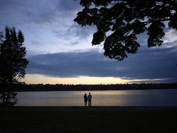 Young couple stand in front of the green lake park before sunset.