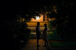 Young couple standing and staring at each other and say goodbye after dating in summer black night. Boyfriend accompanying girlfriend to home. Side view.
