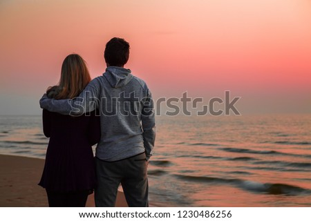 Young couple standing and staring at small waves of sea and pink sunset light. Peaceful atmosphere in summer evening. Back view. Empty place for romantic text, quote or sayings on nature background.