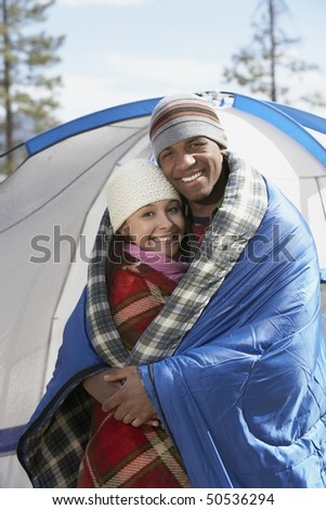 Young couple standing at campsite, wrapped in blankets.