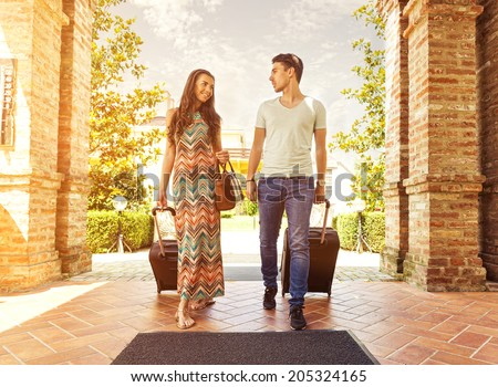 Young couple standing at hotel corridor upon arrival, looking for room, holding suitcases #205324165