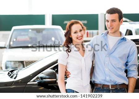 Young couple standing embracing near a car in the showroom
