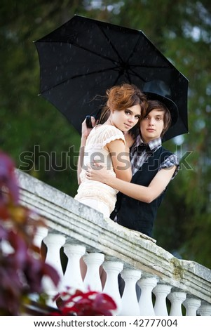 Young couple standing in the rain.