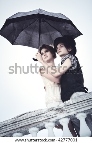 Young couple standing in the rain. Soft blue tint.