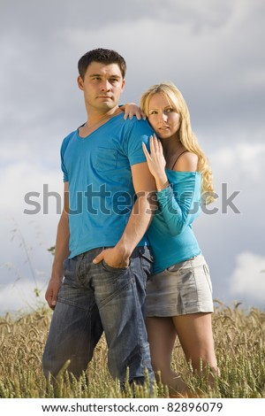 young couple standing in wheat field
