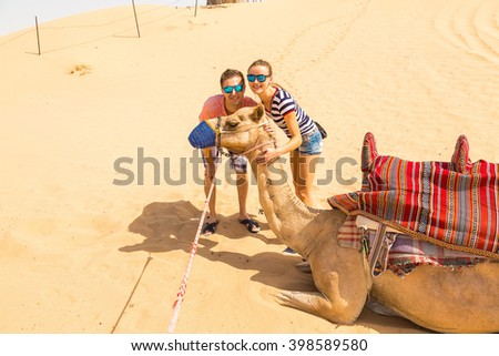 Young couple standing near a camel in a desert taking photo with it near Dubai