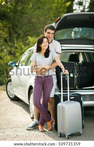 Young couple standing near the opened car boot with suitcases, looking to the camera, outdoors