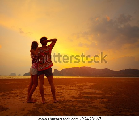 Young couple standing on a beach and looking to a sunset sky