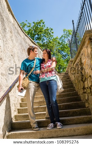 Young couple standing on stairs smiling looking at each other