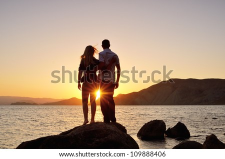 Young couple standing on the shore in the arms and looks at the setting sun by the sea