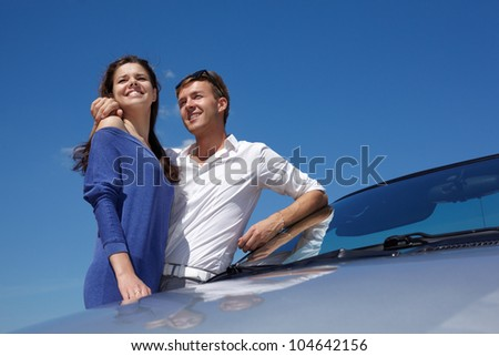 Young couple stands leaning a cabriolet windshield