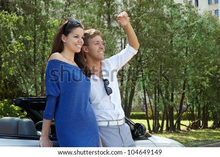 Young couple stands near the car, looking one way, the guy waves his hand to someone