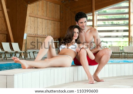 Young couple staying together at the edge of a swimmingpool at spa centre