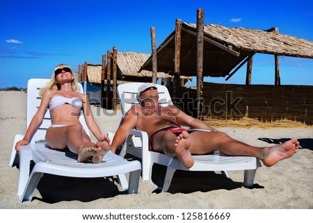 Young couple sunbathe on the beach bed on the sea beach against blue sky