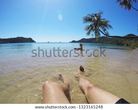 Young couple sunbathing in a sea near palm at wild beach at summer vacation