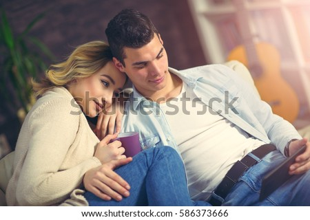 Young couple surfing on the web at home. Smiling woman and man checking mail together on tablet. Happy young couple sitting on sofa and working on digital tablet. - Shutterstock ID 586373666