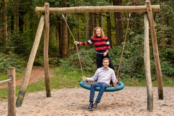 Young couple swings in the playground. the amn and wife are in love. They look happy and laugh in the woods. The woman is behind the man.