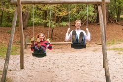 Young couple swings in the playground. the man and wife are in love. They look happy and laugh in the woods.