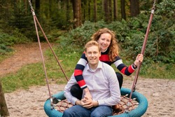Young couple swings in the playground. the man and wife are in love. They look happy and laugh in the woods. They sit together on a large swing.
