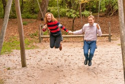 Young couple swings in the playground. the man and wife are in love. They look happy and laugh in the woods. they swing hand in hand.