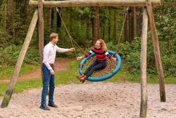 Young couple swings in the playground. the man and wife are in love. They look happy and laugh in the woods. The man pushes the woman on the swing.