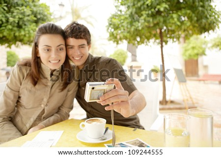 Young couple taking a picture of themselves while in a terrace bar on vacation in a picturesque town square, smiling.
