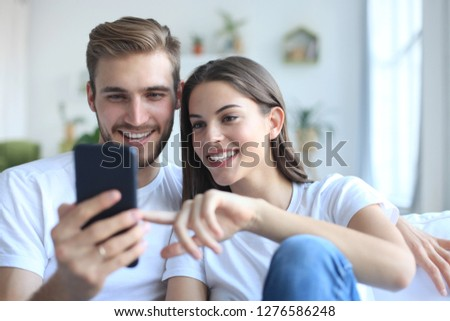 Young couple taking a selfie on couch at home in the living room.