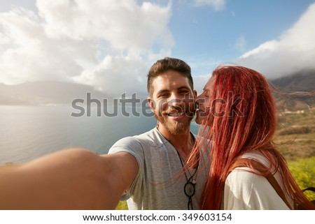 Young couple taking a selfie outdoors. POV shot man holding a camera and taking a self portrait with woman kissing him. #349603154