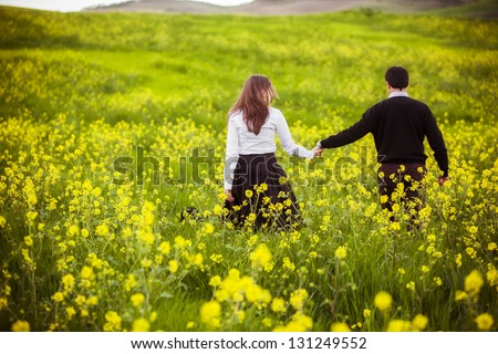 Young couple taking a walk on beautiful flower field.