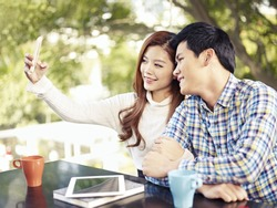 young couple taking selfie in coffee shop.