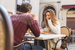 Young Couple Talking at Coffee Shop on a date. Loving couple having fun at a restaurant.