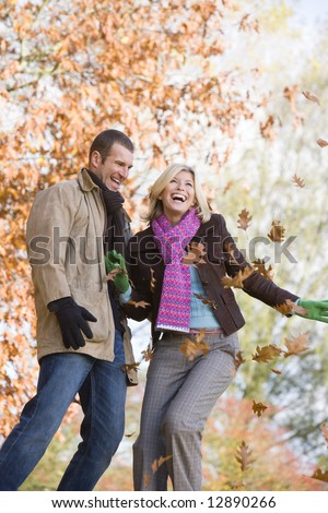 Young couple throwing autumn leaves in the air