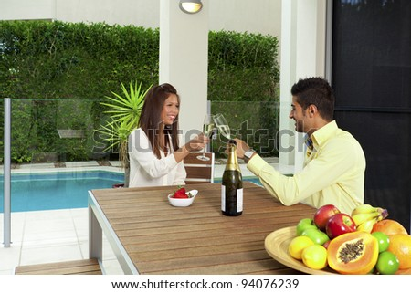 Young couple toasting with champagne in a modern backyard