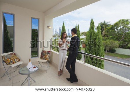Young couple toasting with champagne on a modern balcony for Balcony overlooking city