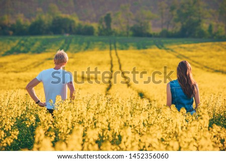Young couple together outside in spring canola field. romantic photo, edit space #1452356060