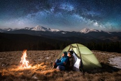 Young couple tourists enjoying in the camping at night, having a rest near campfire and green tent under beautiful night sky full of stars and milky way. On the background snow-covered mountains