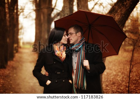 young couple under an umbrella in the autumn forest - stock photo