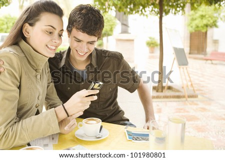 Young couple using a cell phone and writing postcards in a coffee shop while on vacations.