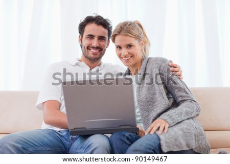 Young couple using a notebook in their living room