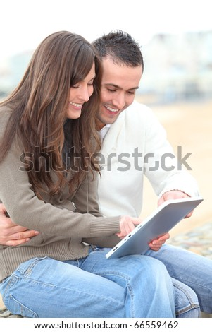Young couple using electronic pad by the beach in winter