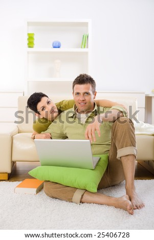 Young couple using laptop computer at home, sitting on floor and lying on couch, embracing.