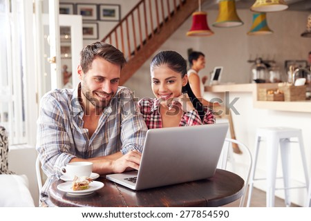 Young couple using laptop in a cafe