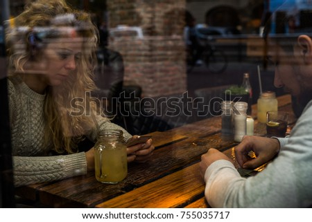 Young couple using mobile phone and drinking healthy juice while they waiting  for dinner in restaurant. Reflection.