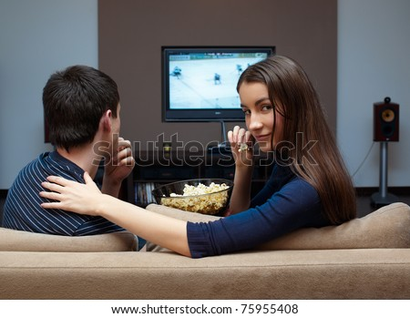 Young couple waching  movie on tv