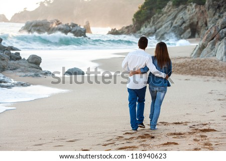 Young couple walking along lonely beach at sunset.