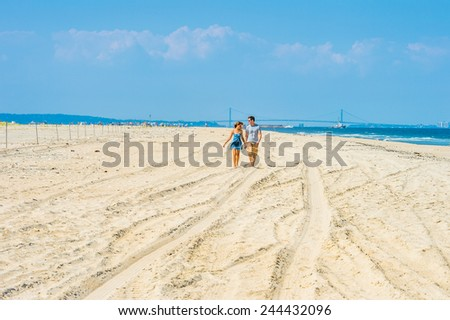 stock-photo-young-couple-walking-and-talking-on-sandy-beach-wearing-sunglasses-guy-wearing-gray-t-shirt-244432096.jpg