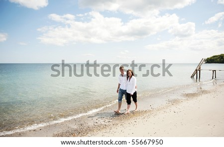 young couple walking at the sea smiling