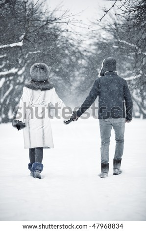 Young couple walking in a park. Backside view.