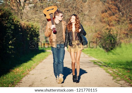 Young couple walking in a romantic mood with guitar outdoors in a park.