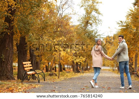 Young couple walking in park on autumn day #765814240